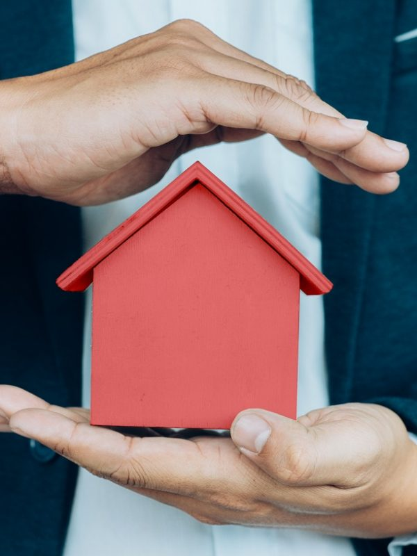 Business man hand hold the house model  saving small house. House insurance