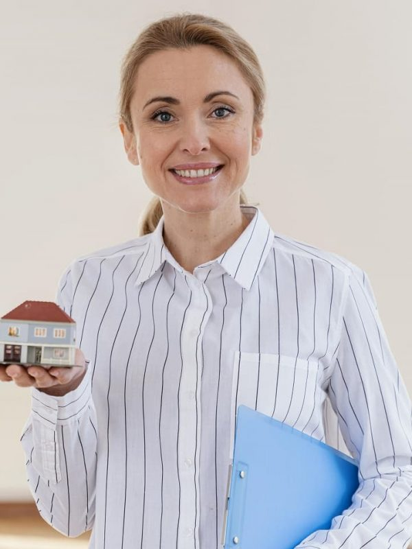 front-view-of-smiley-female-realtor-holding-miniature-house-min